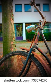 Rusty Bicycle in front of modernbuilding.