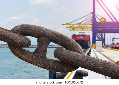 The rusty big anchor chain of the heavy cargo winch A large cargo ship on the background