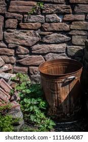 A rusty bin in front of a stone wall in portrait orientation