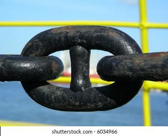 Rusty, black metalic anchor chain on a ship