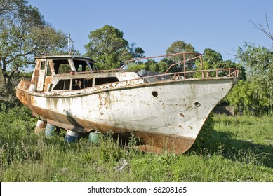 A rusty boat leaning on barrels on the grass, with trees, weeds and a blue sky in the background