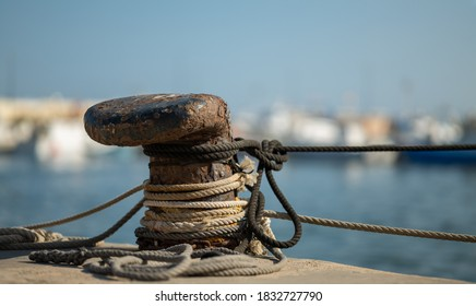 A rusty bollard with ropes. Fishing boats moor here in the port of Santa Pola in Spain. The background is out of focus with nice bokeh.