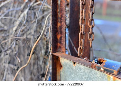 rusty, broken lock and chain, thieves. old rusty lock and a metal chain, bolted on a broken wooden door close-up. In the door panels there are a number of damages, and several bars have been broken.