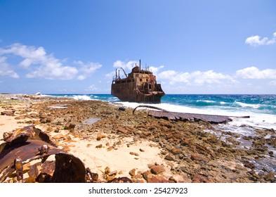 rusty caribbean shipwreck washing ashore on little curacao