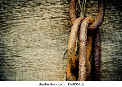 rusty chain on a wooden plank closeup