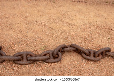 Rusty chains. Selective focus on a old big rusty ships anchor chain in the sand near the sea with large copy space. Abstract background on sand.