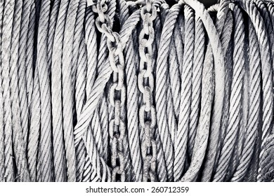 Rusty chains and wire cables as a background image in black and white