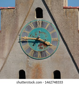 "Rusty clock of catholic parish church ""St. Ulrich"" in Mengen - Rulfingen, Bavaria, Germany. Golden fingers and numbers on green/black clock face. A pigeon sits on the fingers. Time on clock: 03h46"