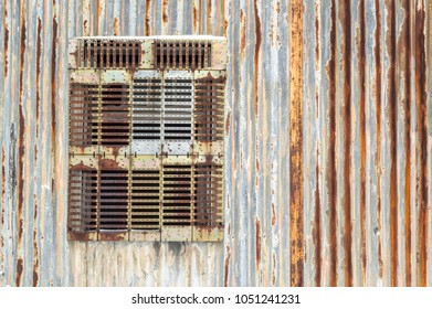 Rusty corregated metal wall with screened window.