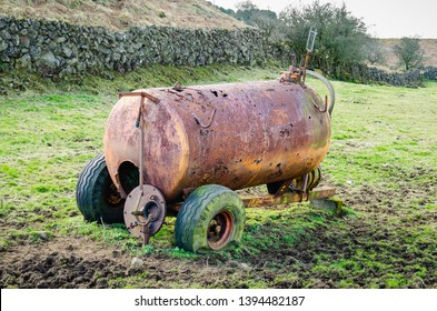 A rusty, corroded slurry tanker with punctured tyres sits abandoned in a muddy field in the Irish countryside.