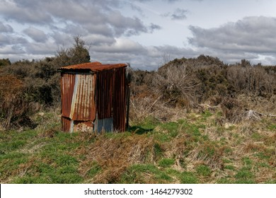 A rusty corrugated iron back country toilet or outhouse on the west coast of New Zealand.