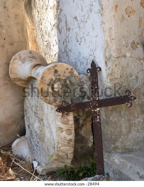 A rusty cross leaning against an original Roman era capital, outside a church in Crete, Greece
