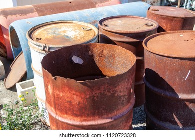 Rusty and damaged 55-gallon steel drums with and without secured lids