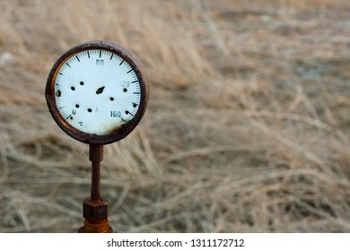 A rusty damaged dial of Czechoslovak manufacture that was used for measuring temperature inside a slag heap near the city of Kladno, Czech republic. Brownfield scene, dead grass is in the backround.