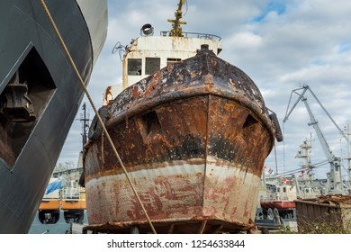 Rusty decommissioned marine ship that was left on the shore.