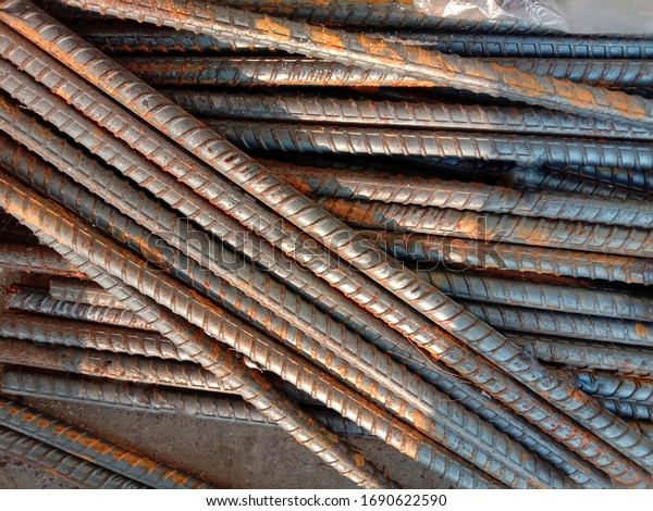 Rusty deformed steel bars pile on cement flooring background closeup in construction site.