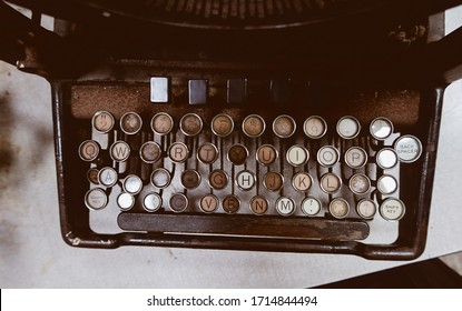 A rusty dirty old decaying vintage antique type writer sat in an office on a table. Scary abandoned horror story typewriter with orange and brown rust. story telling equipment