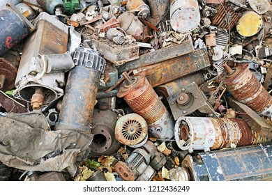 Rusty engines stacked in the scrapyard. Engine parts greased and covered with rust. Dump of pieces of iron and wrecking machinery parts. Scrap yard for recycle the old engine, engine junkyard