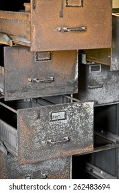 A rusty filing cabinet with empty drawers, pulled open.