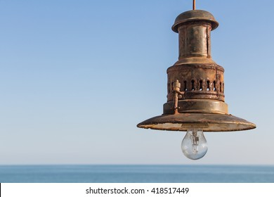 Rusty fishing lamp on a blue sky with sea