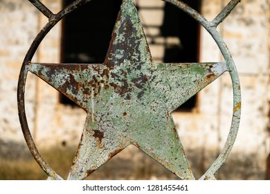 Rusty five-pointed star in an iron fence of a deserted industrial site