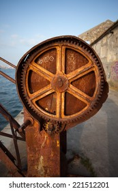 Rusty gear of a crane at river waterfront.