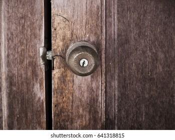 The rusty handle of the door and the old door.