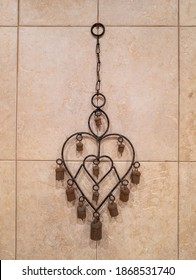 Rusty heart shaped decoration on a beige tiled wall