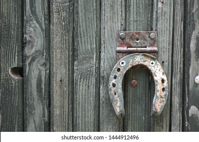Rusty horseshoe on fence. Old rusty iron horseshoe nailed to wooden fence close up. Tradition concept. Horseshoe symbol of luck.
