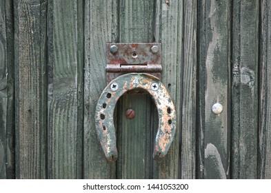Rusty horseshoe on fence. Horseshoe symbol of luck. Old rusty iron horseshoe nailed to wooden fence close up. Tradition concept.