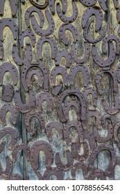 Rusty horseshoes on the wooden door - vertical
