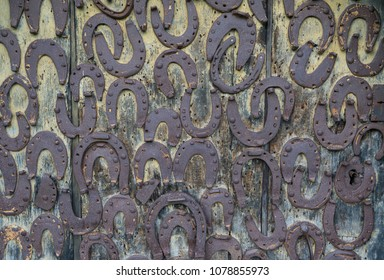 Rusty horseshoes toed on the old wooden door - horizontal