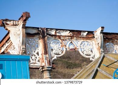 rusty iron balustrade, showing ornamental white painted ironwork on an edwardian seaside pier
