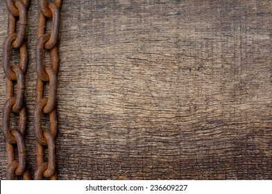 rusty iron chain on the side on a wooden texture background for themes