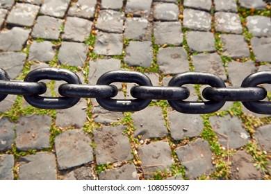 rusty iron chain over cobblestone ground