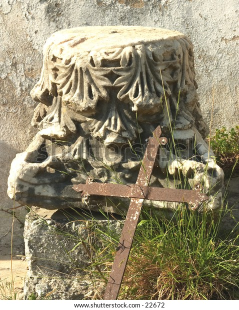 A rusty iron cross leaning against the capitol of a Roman Empire period marble column. In Argiroupolis (Lappa) village, Crete, Greece.