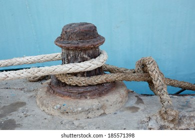 Rusty iron mooring mast and old rope