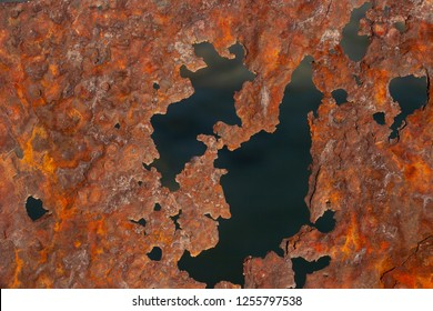 Rusty iron sheet. Fatal oxidation of metal. A dead ship destroyed by the sea.