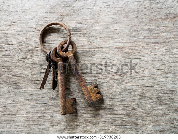 The rusty key and old wooden background