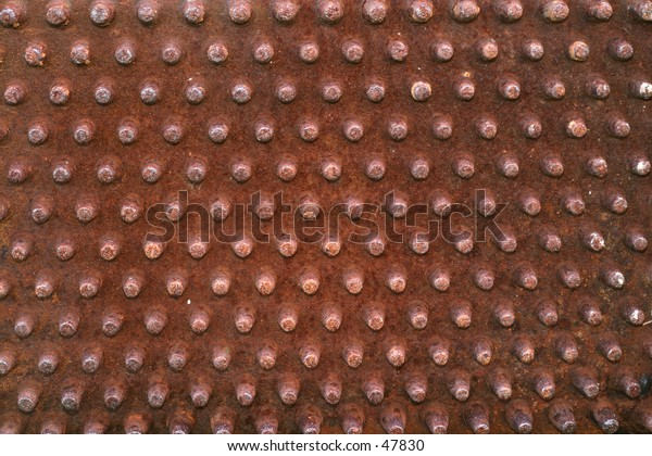 Rusty knobs or prongs from some old machinery. Ideal background image.