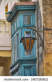 Rusty lantern in front of a typical balcony on Malta.