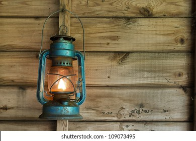 Rusty lit blue lantern hanging in an old shed