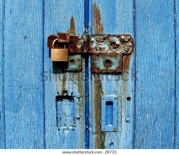 Rusty lock and hinge, on old blue gates.