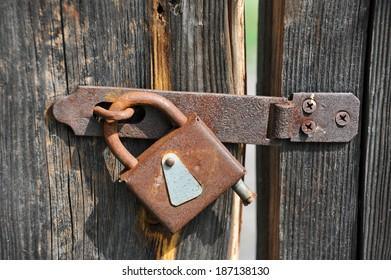Rusty lock on old vintage rural wooden gate
