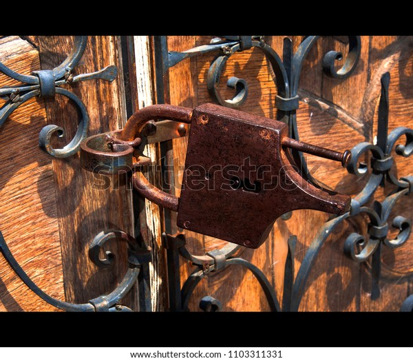 rusty lock on a wrought iron grilled door