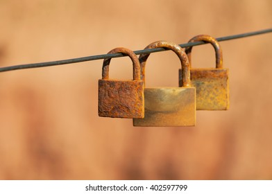 Rusty love locks hanging on sling, as a symbol of eternal love and endless love. Red rock background. Selective focus.