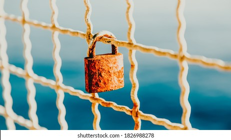 Rusty love padlock hanging on a bridge on a light blue sea background. 16 on 9. Makarska, Croatia