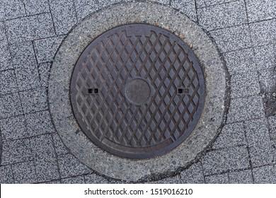 Rusty manhole cap, grunge manhole cover, round.