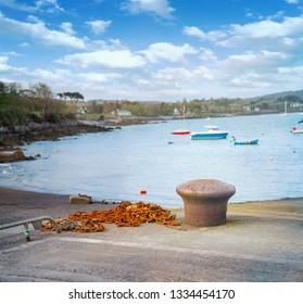 Rusty marine mooring bollard and rusty chain in a Castletownbere harbor. County Cork, Ireland.