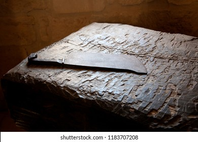 rusty meat cleaver on an old and well worn butcher's block